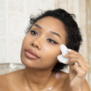 woman practicing facial gua sha